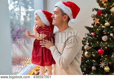 winter holidays and family concept - happy middle-aged father and baby daughter looking through window over christmas tree at home
