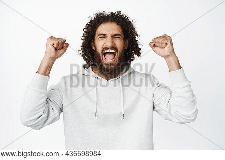 Portrait Of Cheerful Hispanic Man Winning, Shouting From Joy, Clench Fists And Celebrating, Triumphi