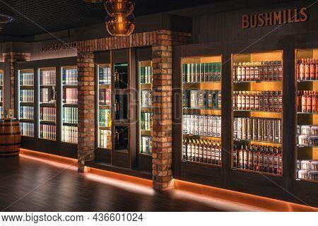 Bushmills, Northern Ireland, Aug 2019 Variety Of Bushmills Whiskey In A Rows On Illuminated Shelf On
