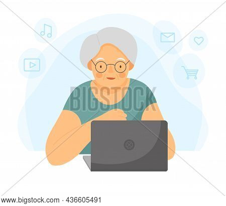 Happy Grandmother With Laptop. An Old Woman Is Working On A Laptop. Grandma Is Sitting At The Comput