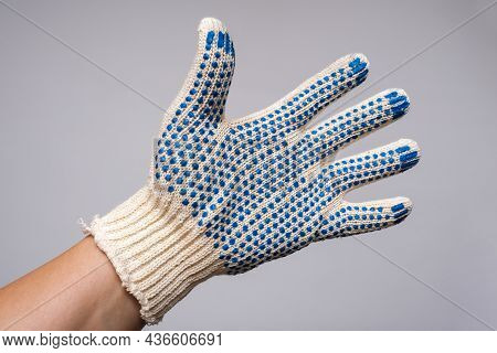 Hand Wearing Construction Worker Protective Knitted Dotted Gloves On Grey Background, Hand Protectio