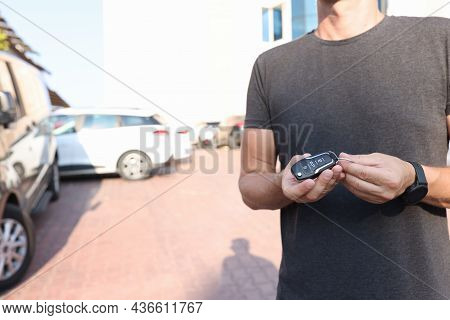 Man Holds In Hands Push-button Remote Control From Car Closeup