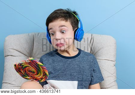 8 Year Old Brazilian Child, With Headphone, Holding A Colorful Lollipop And Making A Face.