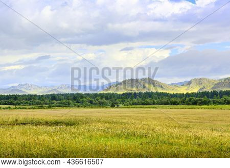 A Grassy Plain Against The Background Of Green Mountains In Summer Under A Blue Cloudy Sky. Siberia,
