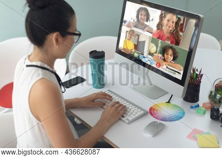 Asian girl holding computer for video call, with smiling diverse elementary school pupils on screen. communication technology and online education, digital composite image.