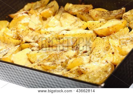 Roasted potatoes with spices and cheese as background poster