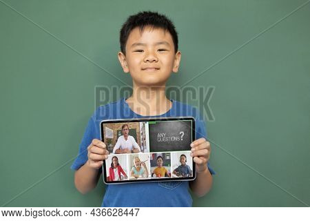 Smiling asian boy holding tablet for video call, with diverse elementary school pupils on screen. communication technology and online education, digital composite image.