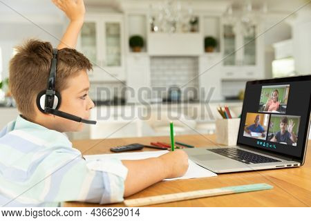 Caucasian boy raising hand for video call, with smiling diverse elementary school pupils on screen. communication technology and online education, digital composite image.