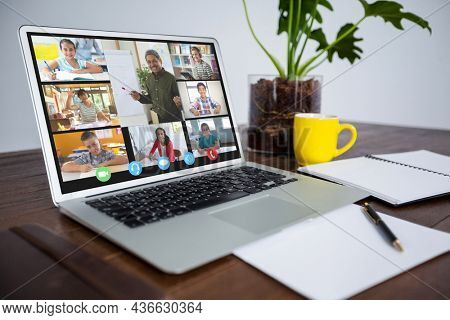 Smiling diverse elementary school pupils during class on laptop screen. communication technology and online education, digital composite image.