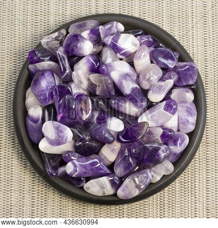 Set Of Various Amethyst Natural Mineral Stones And Gemstones On Black Plate And Grey Background Top