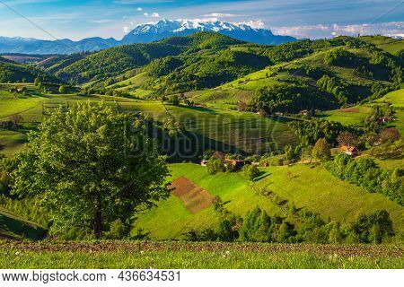 Amazing Spring Countryside Landscape, Houses And Farmlands On The Hills. Beautiful Snowy Mountains I