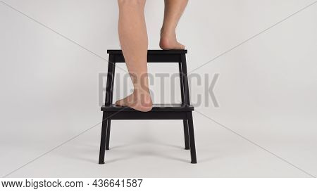 Legs And Barefoot Is Step Up And Turn Around On Step Stool Or Wooden Stairs On White Background.