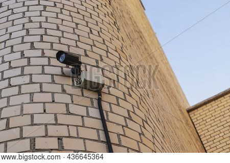 Surveillance Camera On The Facade Of A Residential Brick Building. Security. Control Over The Observ