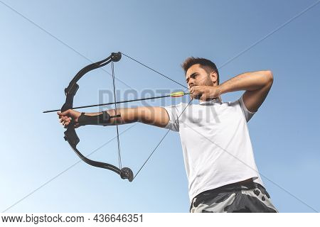 Man With Bow And Arrow Practicing Archery Outdoors, Low Angle View