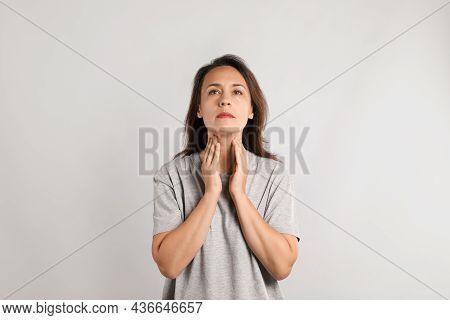 Mature Woman Doing Thyroid Self Examination On Light Background