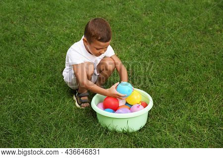 Little Boy With Basin Of Water Bombs On Green Grass