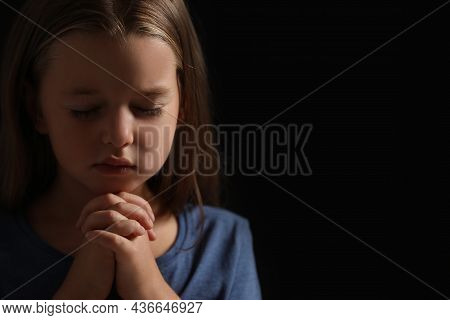 Cute Little Girl With Hands Clasped Together Praying On Black Background. Space For Text
