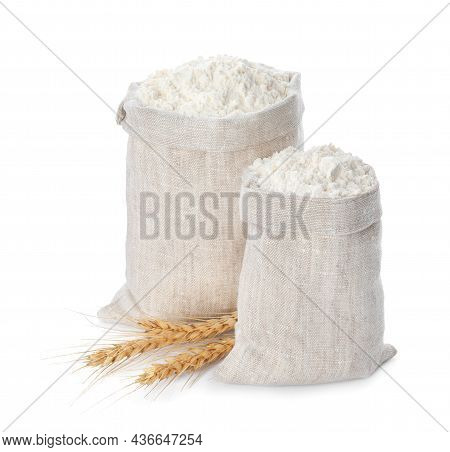 Sacks With Flour And Wheat Spikes On White Background