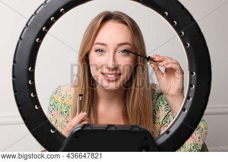 Beautiful Young Woman Applying Mascara On Eyelashes Near White Wall, View Through Ring Lamp