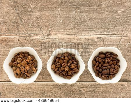 Light Roasted, Medium Roasted And Dark Roasted Speciality Arabica Beans In White Bowls Over Brown We