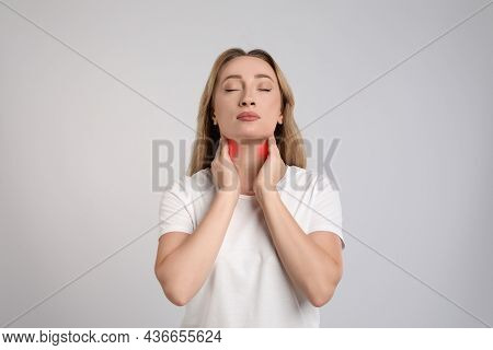 Young Woman Doing Thyroid Self Examination On Light Grey Background