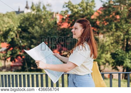 Attractive Young Female Tourist Is Exploring New City. Unhappy Redhead Woman With Map In Hands Lost
