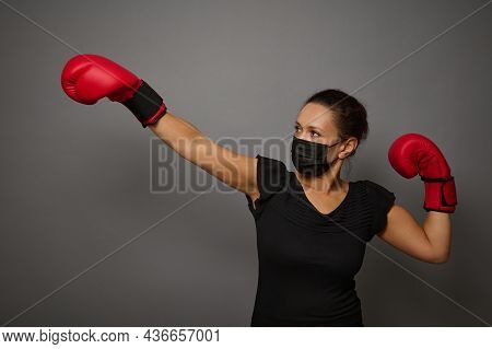 Young Athletic Woman In Safety Protective Medical Mask And Red Boxing Gloves Punches An Imaginary Pu