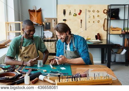 Portrait Of Smiling Male Artisan Teaching Young Apprentice In Leatherworkers Workshop, Copy Space
