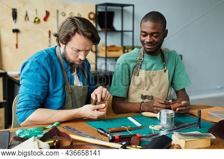 Portrait Of Modern Male Artisan Teaching Young Apprentice In Leatherworkers Workshop, Copy Space