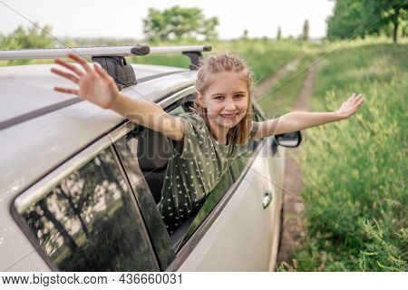 Beautiful preteen girl sitting in the car and looking out the window open, smiling and holding hands up in the field. Happy child kid in the vehicle outdoors during summer journey
