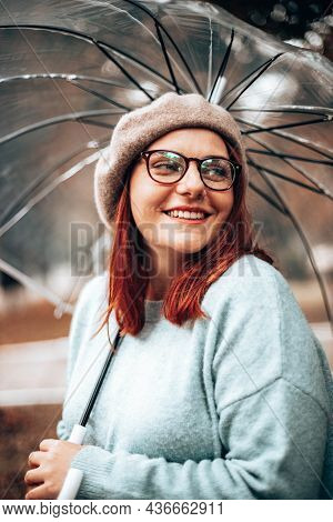 Young Surprised Girl With Glasses And Transparent Umbrella In The Park, Look At The Camera. Transpar