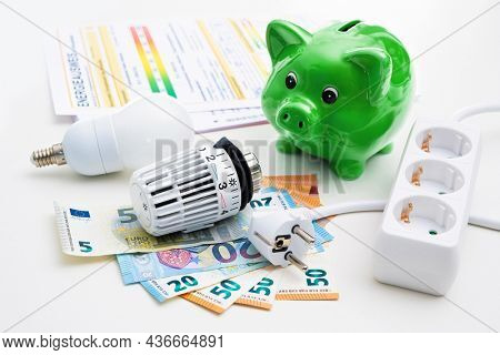 Energy cost, saving energy concept. Piggy bank with money, plug, bulb and radiator thermostat on white background