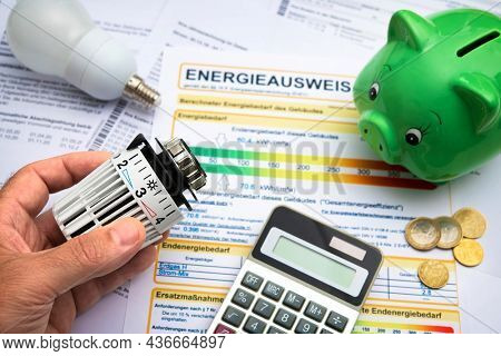 Energy costs concept, saving energy through modernization. Hand with radiator thermostat, calculator and energy certificate