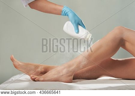 Cosmetologist is sprinkling and distributing talcum powder on a young girl's leg before the epilation procedure. The girl is lying on a couch in a beauty salon, she does the procedure shugaring