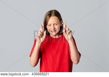 Please, I Need It Badly. Beautiful Brunette Teen Girl Feels Nervous, Crosses Fingers For Good Luck,
