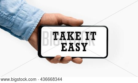 Closeup Of A Male Hand Holding Smartphone With Horizontal Text Take It Easy On Display. Conceptual P
