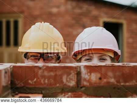 Playful mother and daughter bricklaying