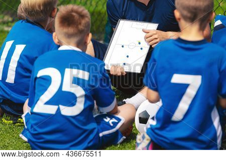 Anonymous Football Coach Teaching Kids On Grass Field. Coach Explains A Game Strategy Using White Bo
