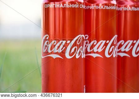Many Cans Of Coca-cola Soda With Background Blurring In A Park.