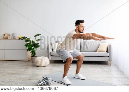 Handsome Young Arab Man Doing Squats, Working Out At Home, Full Length