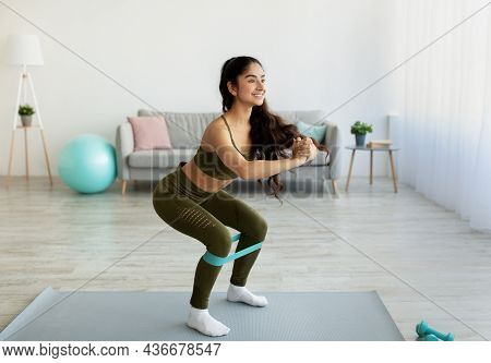 Fit Young Indian Woman Doing Squats With Elastic Band During Home Workout, Copy Space. Domestic Spor