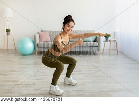 Home Workout Concept. Young Indian Woman Doing Squats And Showing Thumb Up Gesture At Home, Full Len