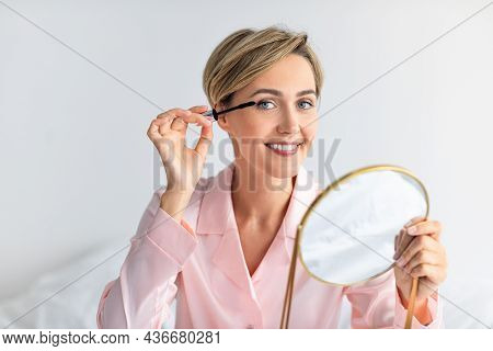Portrait Of Smiling Woman Holding Mirror Applying Mascara