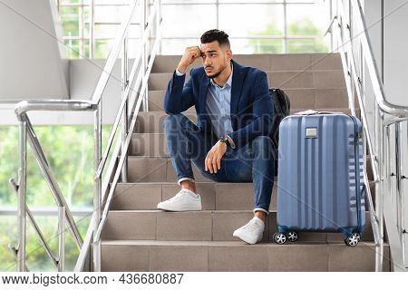 Flight Cancellation. Upset Arab Man Sitting With Luggage At Stairs In Airport
