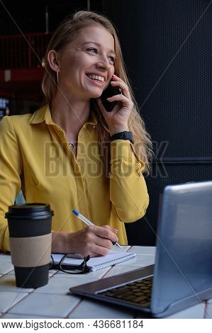 Young Well Dressed Cauasian Woman Sitting At Table, Calling By Smartphone. Beautiful Lady Using Cell
