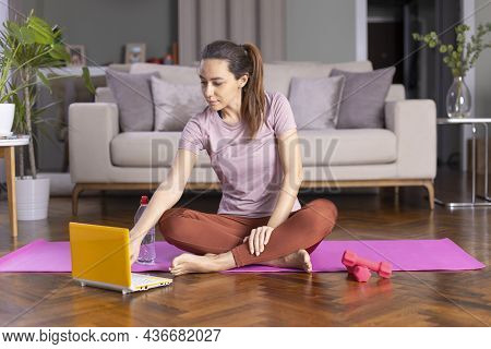 Young Sporty Woman Dressed In Sportwear Watching Helpful Videos On The Internet
