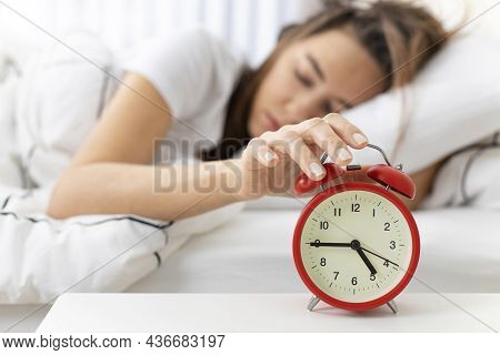 Wake Up Of An Asleep Young Woman Stopping Red Alarm Clock On The Bed In The Morning