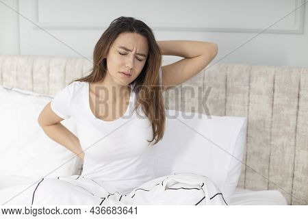 Unhappy Woman Waking Up In Uncomfortable Bed Feeling Ache In Back Pain Massaging Tensed Muscles Of S