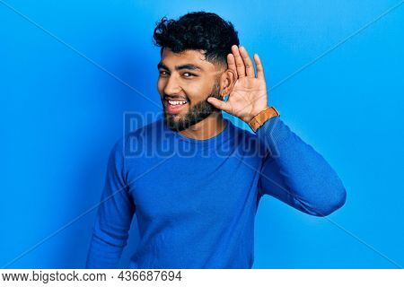Arab man with beard wearing casual blue sweater smiling with hand over ear listening an hearing to rumor or gossip. deafness concept.