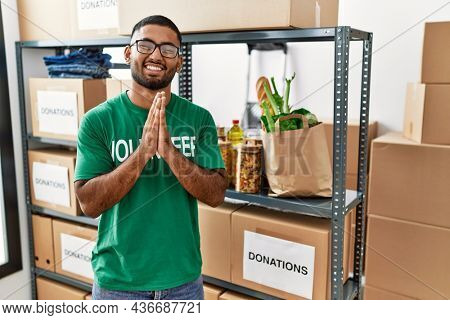Young indian man volunteer holding donations box praying with hands together asking for forgiveness smiling confident.